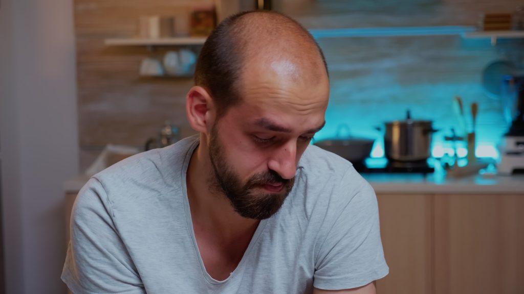 Stressed man working overtime feels eye fatigue