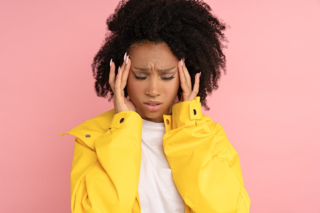 Unhappy Afro woman wear yellow raincoat suffers from severe throbbing headache touching her temples